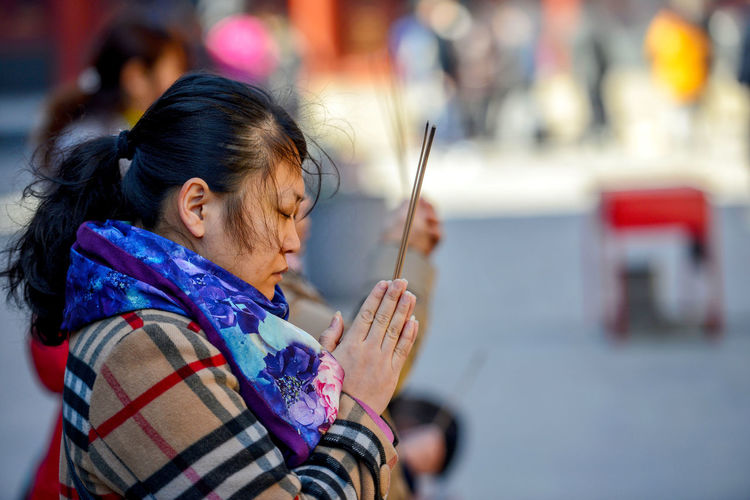 Worshippers hold incense sticks and pray at Yonghegong Lama Temple in Beijing, China. ASIA Beijing Lama Temple Monastery Smoke Worshippers Adult Budhism Casual Clothing China Clothing Day Females Focus On Foreground Hair Hairstyle Headshot History Holding Incidental People Lama Leisure Activity Lifestyles One Person Outdoors Portrait Prayer Real People Religion Scarf Stick Temple Warm Clothing Winter Women Yonghe Yonghegong