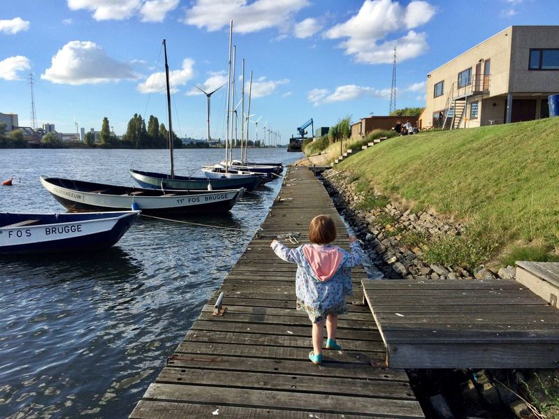 Waterfront Architecture Building Exterior Built Structure Casual Clothing Childhood Cloud Cloud - Sky Day Diminishing Perspective Elementary Age Footpath Full Length Grass Green Color Innocence Leisure Activity Lifestyles Outdoors Person Sky The Way Forward