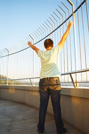Rear view of man standing by railing against bridge