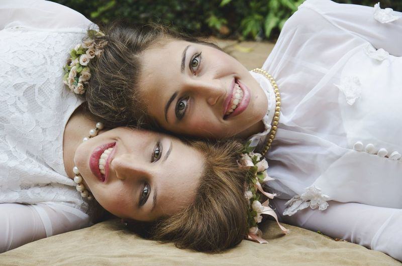 Portrait of smiling bride lying down with friend