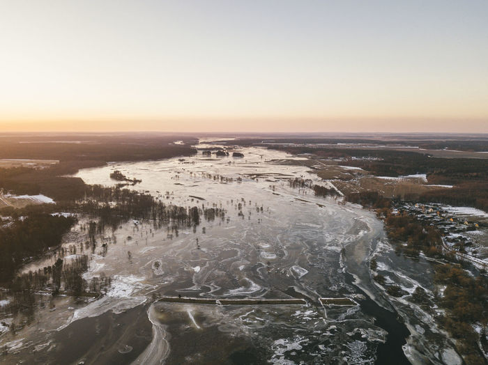 Aerial view of snow covered landscape during sunset