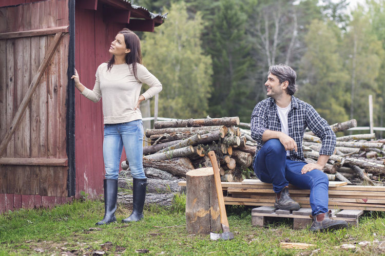 Full length of young couple sitting on wood