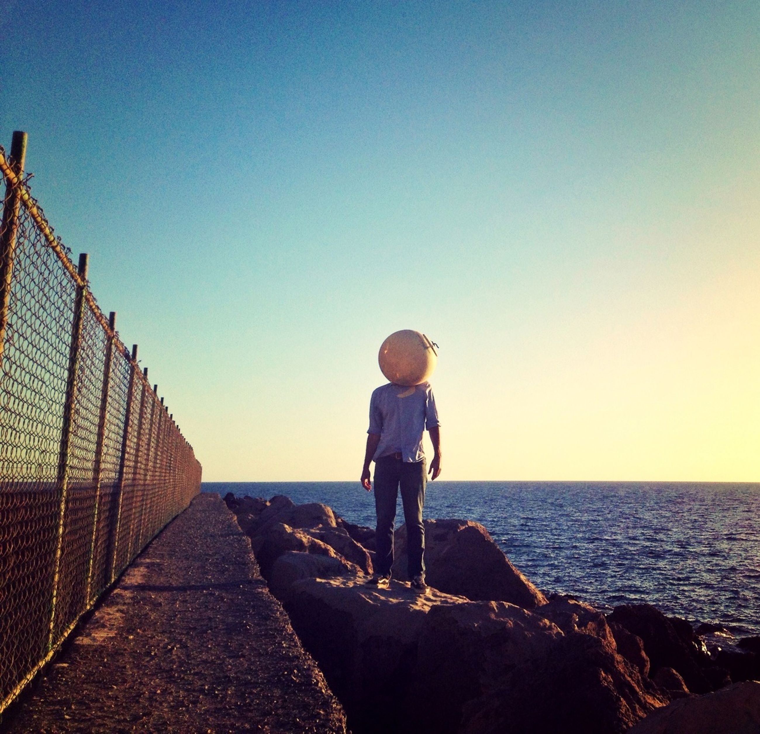 sea, water, horizon over water, clear sky, rear view, full length, copy space, standing, lifestyles, leisure activity, beach, casual clothing, blue, sky, shore, person, built structure, nature