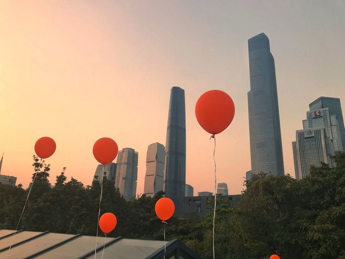 Low angle view of red balloons and buildings against sky during sunset