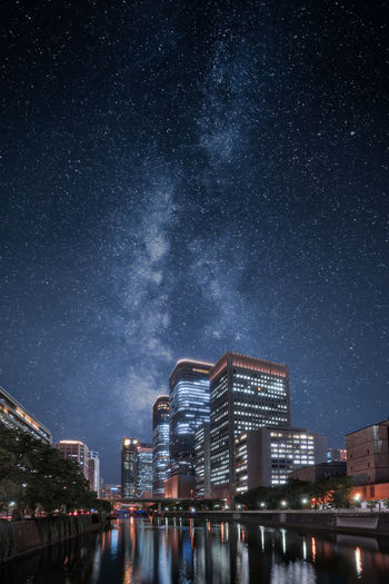 Illuminated buildings against starry sky at night