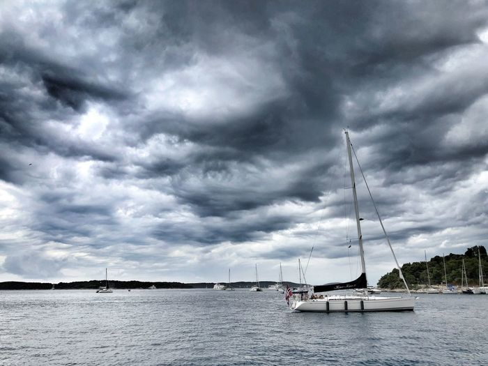 Sailboats in sea against cloudy sky