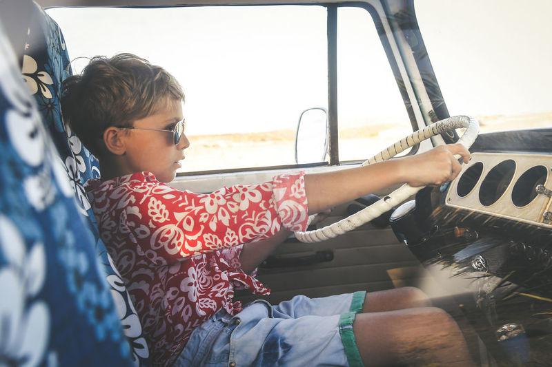 Boy wearing sunglasses driving car
