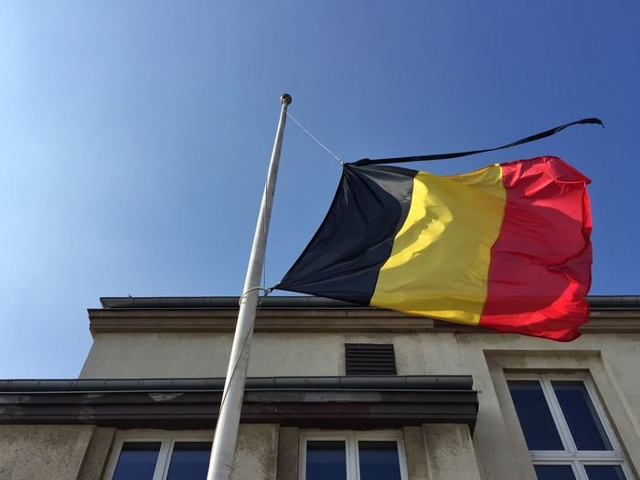 Low angle view of belgium flag waving against building