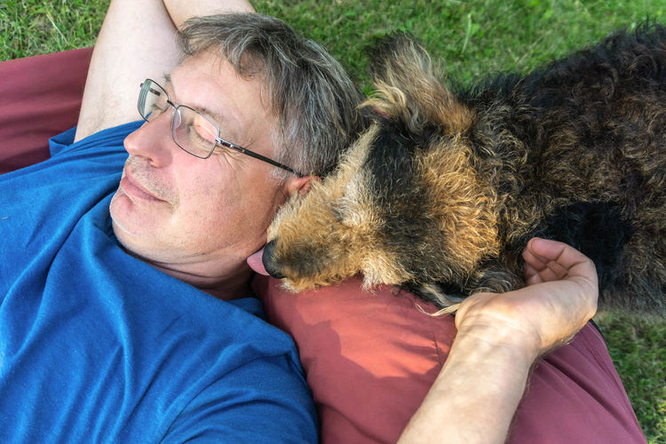 Senior man relaxing on lawn with dog