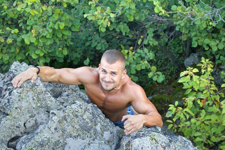 High angle portrait of shirtless muscular man climbing on mountain