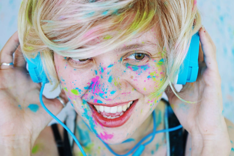 Close-up of happy woman covered in powder paint wearing headphones