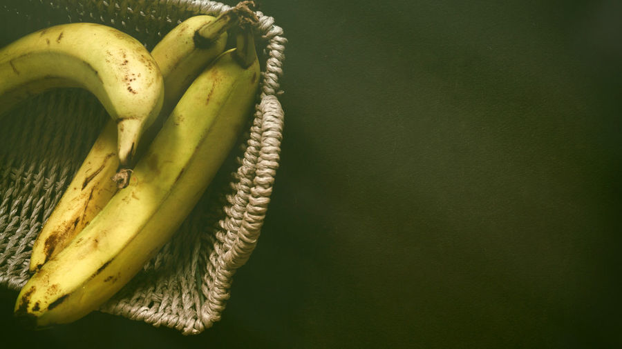 Ripe bananas in fruit basket low key photography on black background  still life simplicity