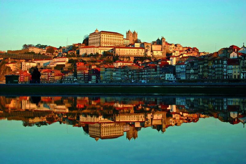 Captions of Porto Building Exterior Architecture Built Structure Reflection Water Sky Waterfront Clear Sky City Building Nature Residential District Lake Outdoors Day Travel Destinations Symmetry Standing Water Reflex Reflection Effect River Riverside Nature Nature_collection