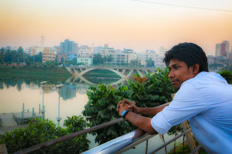 Side view of man leaning on railing against river in city