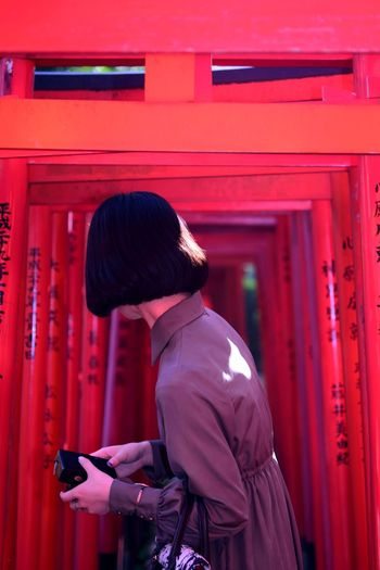 Side view of young woman standing against red torii