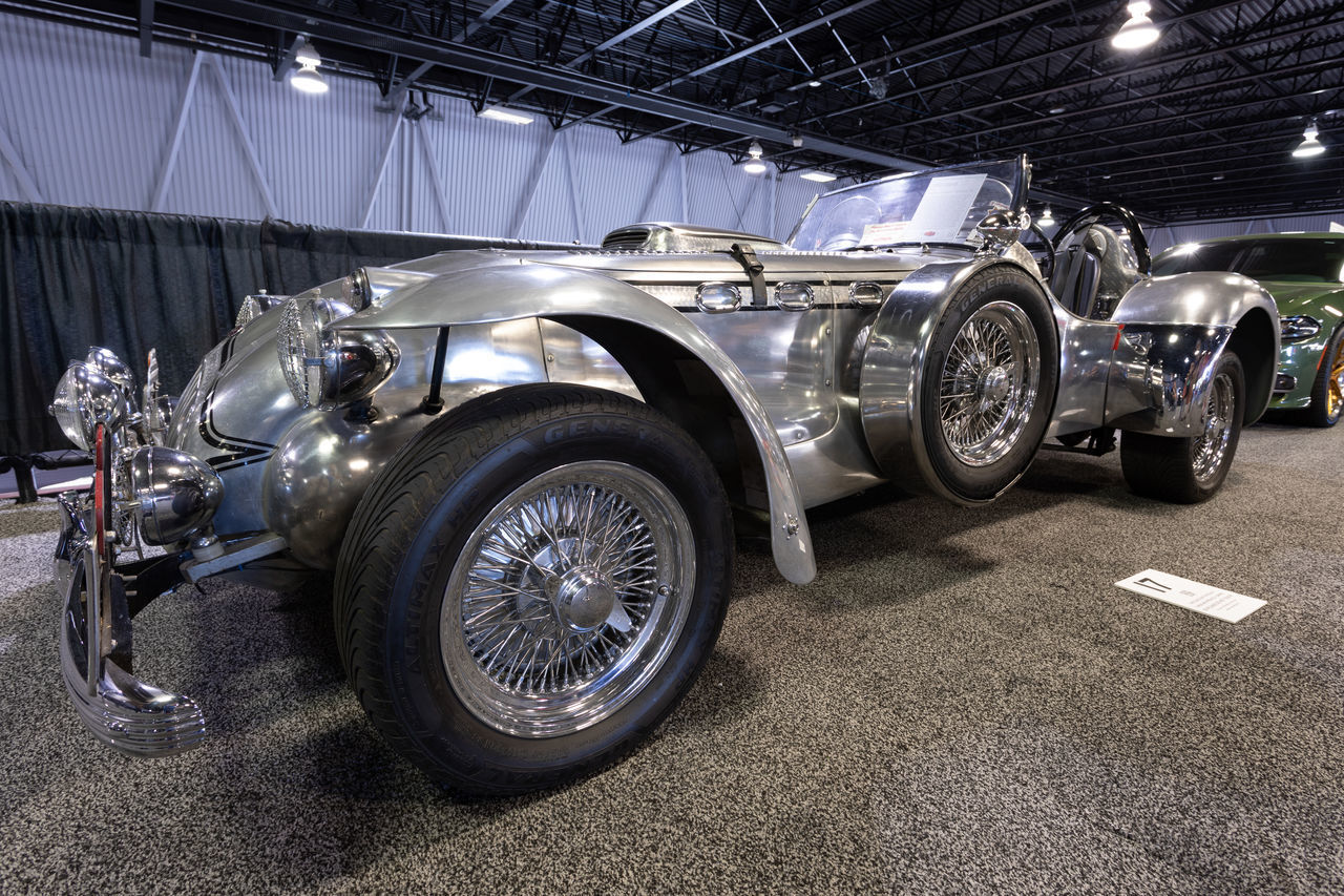 transportation, mode of transportation, land vehicle, motor vehicle, wheel, car, indoors, metal, tire, shopping, stationary, no people, illuminated, large group of objects, in a row, vintage car, retail, wealth, automobile industry, shiny, luxury, garage, silver colored, mechanic