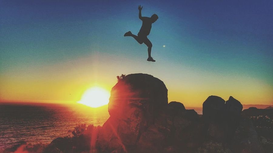 Silhouette Of Man Jumping Against Sky During Sunset