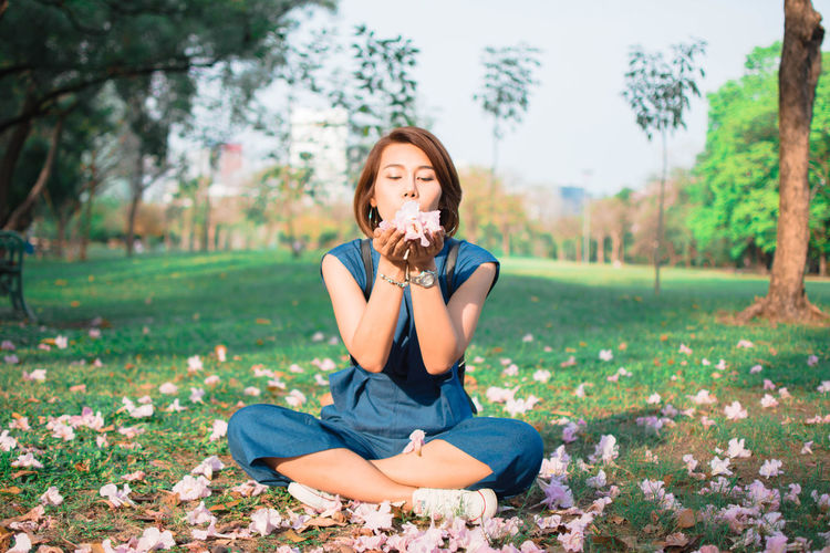 Woman Blowing Flowers While Sitting On Field At Park