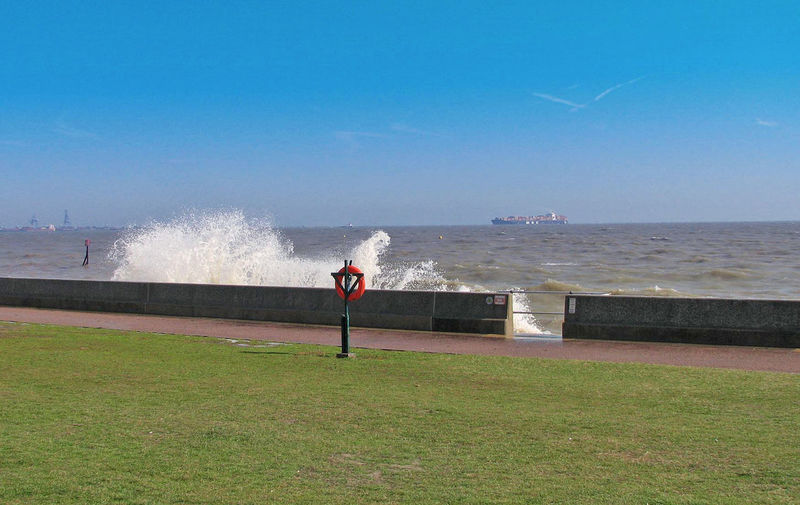 Crashing waves over the sea wall, with distant view of a large container ship from China bound for Felistowe Docks - Dovercourt Beach, Harwich, Essex, UK Chinese Shipping Container Ship Dovercourt, Harwich Crashing Waves  Day Full Length Grass Horizon Horizon Over Water Land Leisure Activity Life Buoy Lifestyles Men Motion Nature One Person Outdoors Power In Nature Real People Rear View Sea Sky Sport Standing Water Holiday Moments