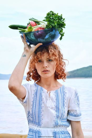 Portrait of young woman carrying bowl with vegetables on head against sea