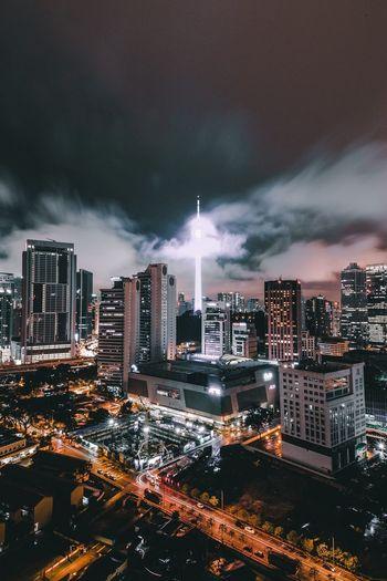Illuminated Cityscape Against Cloudy Sky