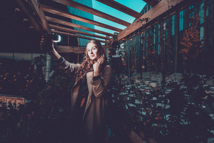 Portrait Of Young Woman Holding Lighting Equipment In Plant Nursery