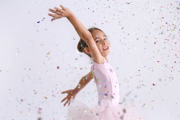 Cute ballerina little girl in pink tutu was dancing with scattering rainbow metallic confetti for happy celebration event in the room, kid ballet Childhood Child One Person Girls Indoors  Innocence Females Leisure Activity Confetti Happiness Lifestyles Real People Enjoyment Emotion Human Arm Women Casual Clothing Looking Arms Raised Excitement
