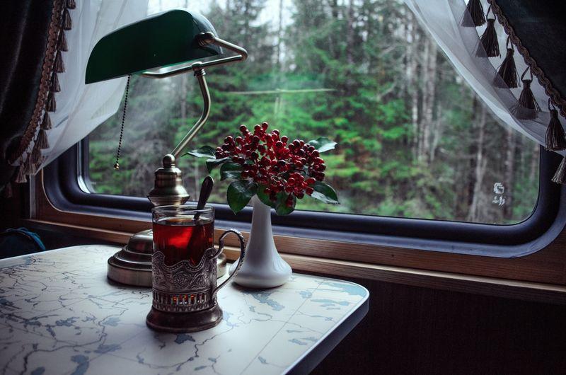 Flower vase on table by window