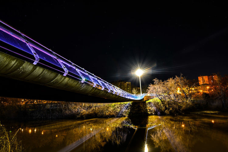 Light trails on bridge over river against sky at night