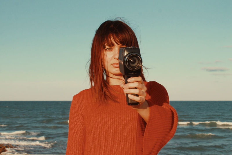 Portrait of woman holding camera at beach against sky
