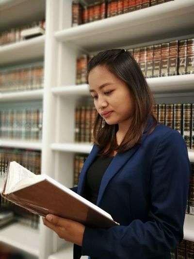 Lawyer reading book in library