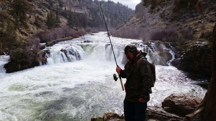 Man swimming in waterfall
