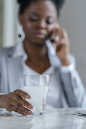 Ill woman holding glass with medicine while talking over phone on table