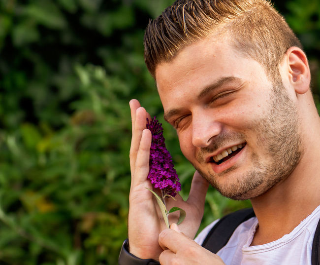 Close-up portrait of young man holding purple outdoors