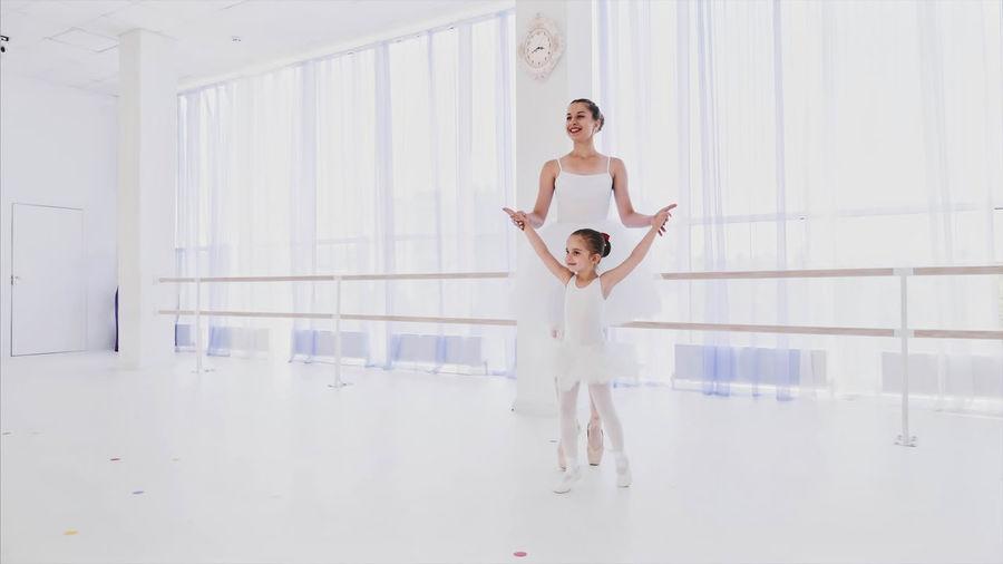 Young woman teaching ballet dance to girl in studio