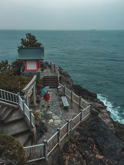 High angle view of man with umbrella against sea
