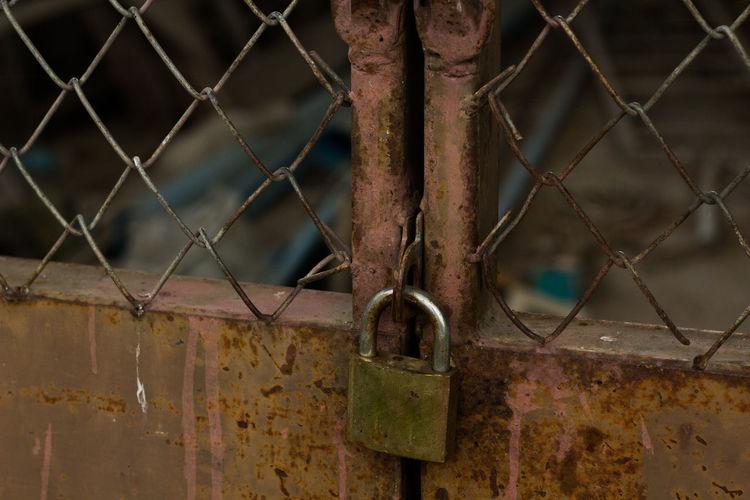 Close-Up Of Padlock On Rusty Gate
