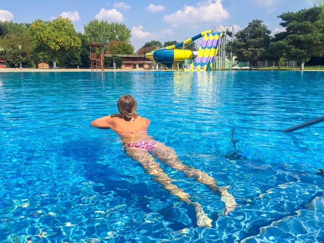 Woman Swimming in the pool Water Full Length Real People Swimming Pool Leisure Activity Blue Vacations Lifestyles Day One Person Sunlight Sky Tree Outdoors Standing Weekend Activities Nature Water Pool Swim Blue Woman One Summer