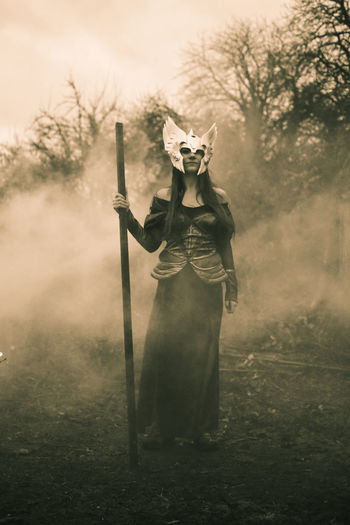Portrait of young woman wearing costume on field during foggy weather