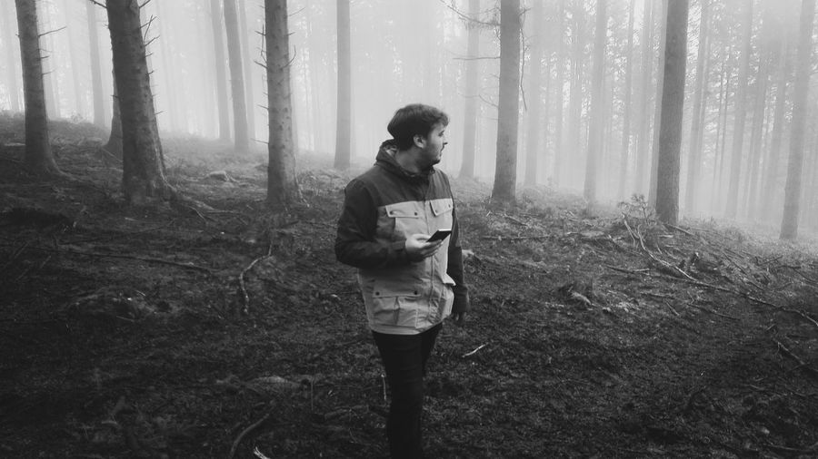 Man using mobile phone in foggy forest