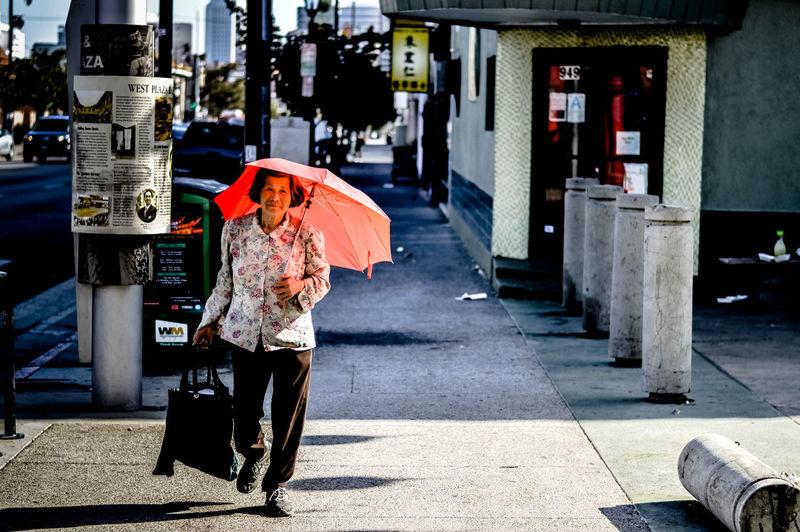 Man walking on footpath in city