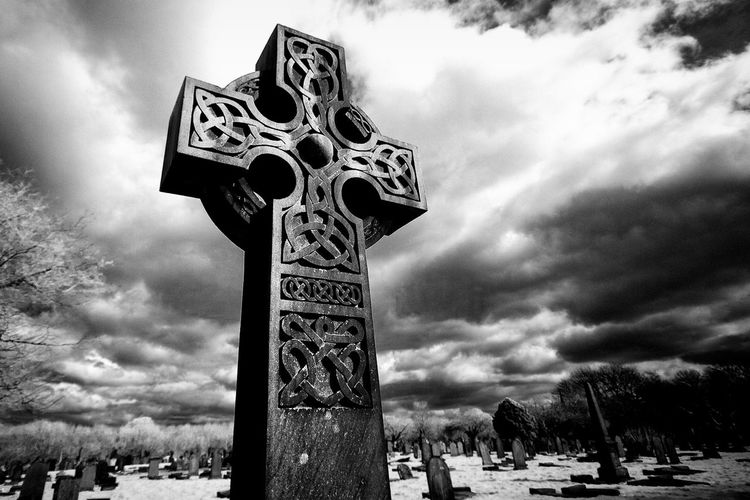 Low angle view of cross at cemetery against sky