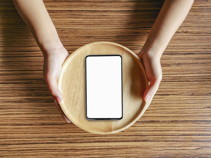 Directly above shot of woman holding smart phone on table