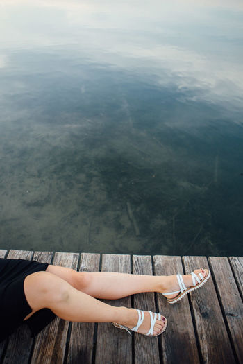 Young woman lying on pier by lake
