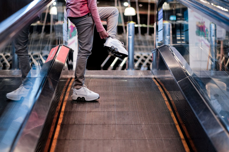 A girl skater on an escalator at the mall