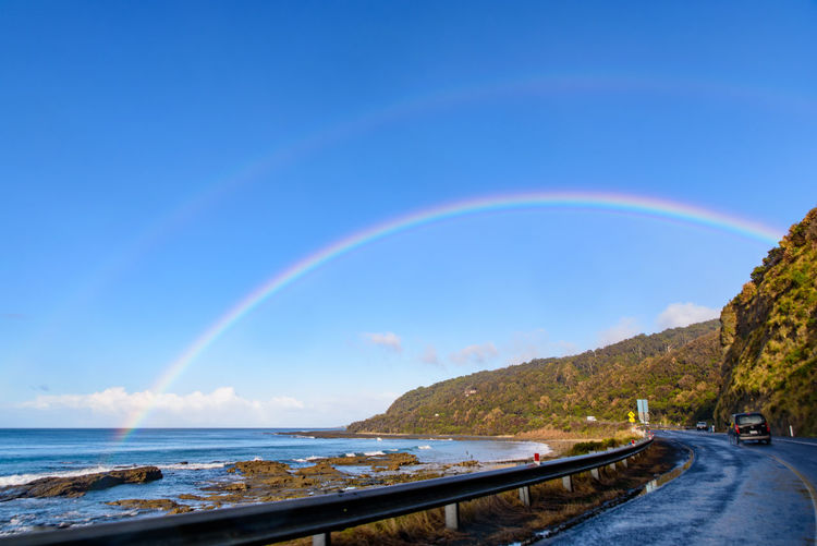 Scenic view of rainbow over sea against blue sky