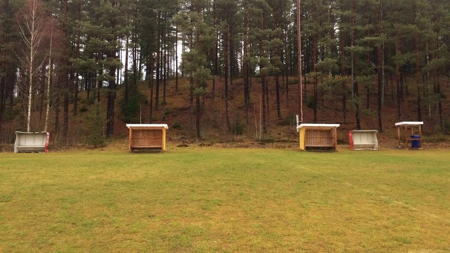 Built structure on field against trees in forest