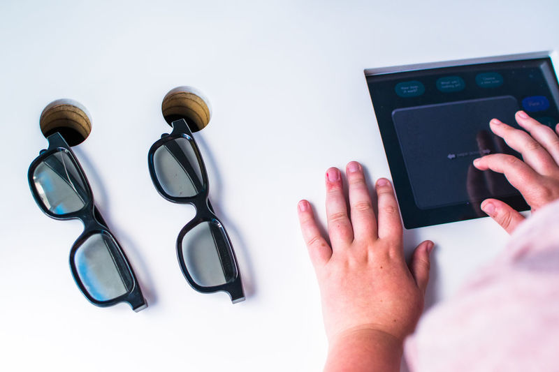 Top view of eyeglasses on wooden table and hands using tablet