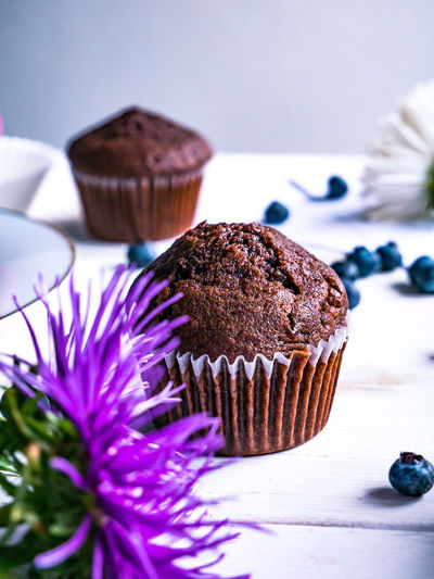 Close-up of flower and muffins on table