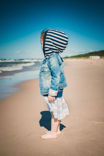 Side view of girl standing at beach